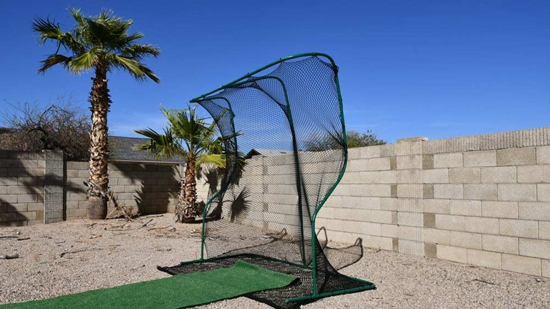 Golf net with roll of fresh lawn carpet